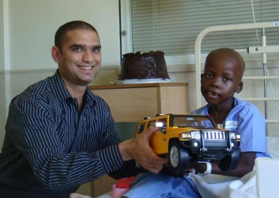 Ismail presenting a seriously ill child with a remote controlled car