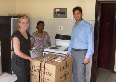 Mr Lockhat and Shuvee present to the matron a brand new gas stove on behalf of the firm