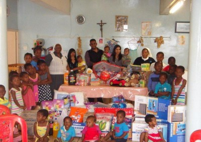 Coastal Accounting Staff and the wonderful Staff and Children from Assisisi posing with some of the donated goods